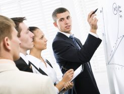 Businessman presenting his ideas on whiteboard to colleagues